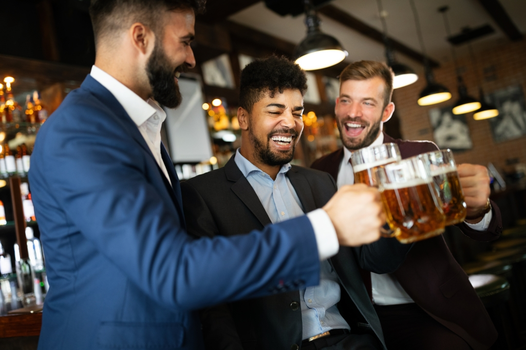 Three people celebrating with beer.