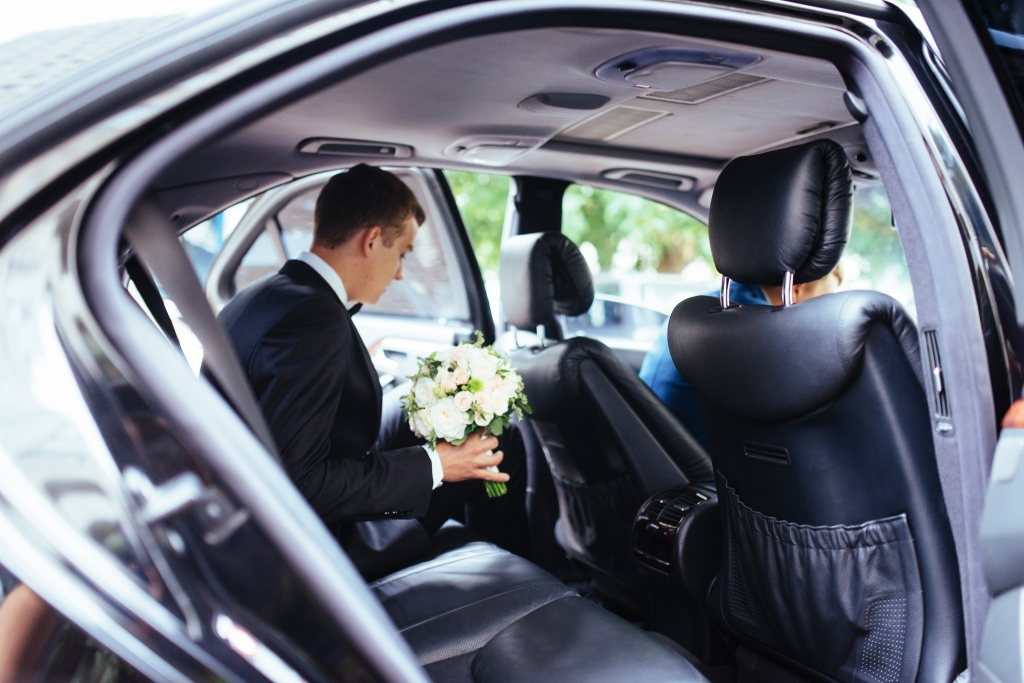 A person in the back of a sedan holding flowers.